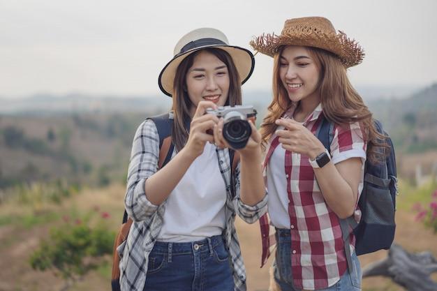 Due donna turistica scattare una foto con la macchina fotografica in natura