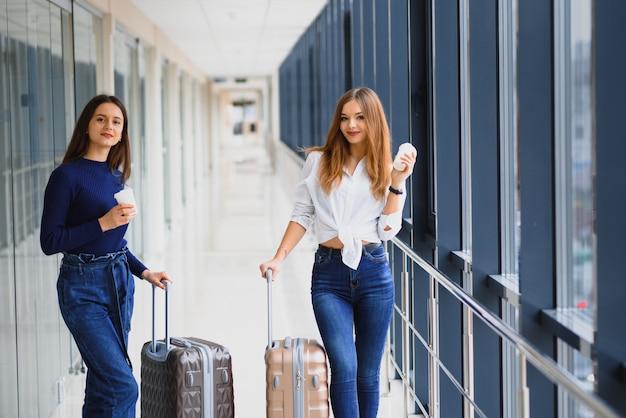 Due donne all'aeroporto vanno su un aereo fidanzate all'aeroporto con le valigie