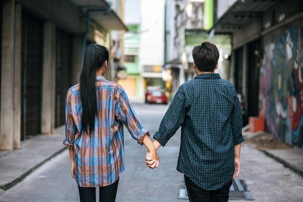 Due donne amorevoli in piedi e mano nella mano sulla strada.