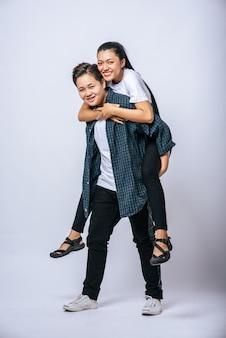 Due donne amorevoli indossavano camicie a righe e cavalcavano la schiena.