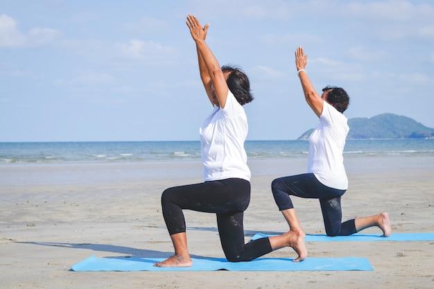 Due donne anziane asiatiche seduto sulla sabbia, facendo yoga in riva al mare
