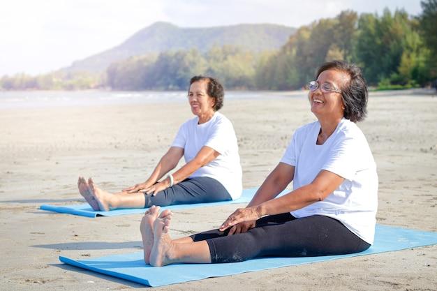 Due donne anziane si esercitano sulla spiaggia, sorriso felice. il concetto di comunità anziana