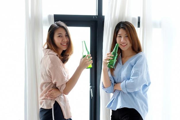 Due donne asiatiche che bevono birra alla festa
