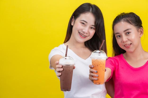 Due donne asiatiche che bevono tè freddo al latte e cacao ghiacciato su un giallo.