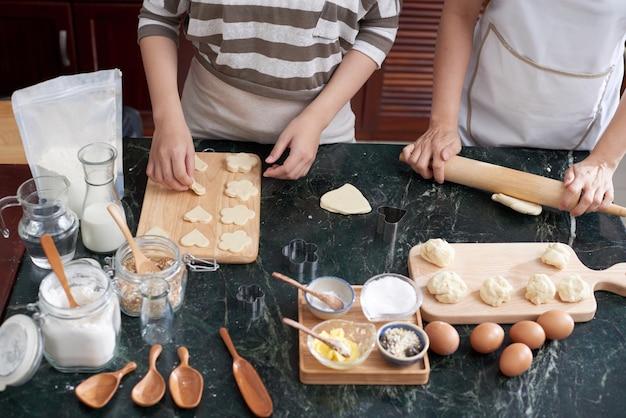 Due donne asiatiche irriconoscibili che rotolano pasta e che tagliano i biscotti sul contatore di cucina