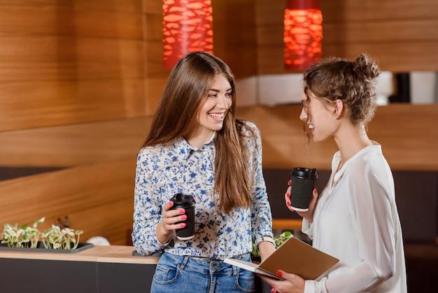 Due donne bellissime che chiacchierano e che tengono le tazze di carta con caffè.
