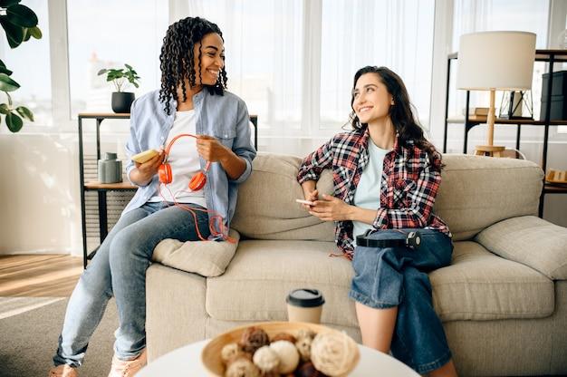 Due donne carine gode di ascoltare la musica sul divano con una tazza di caffè.