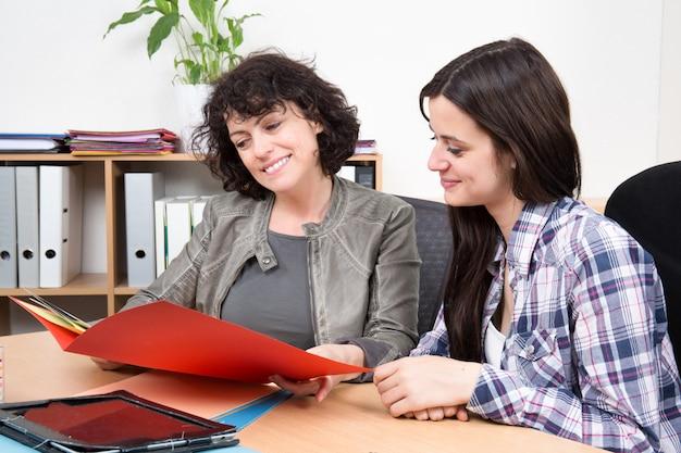 Due donne caucasiche felici di affari che leggono i documenti nel loro ufficio