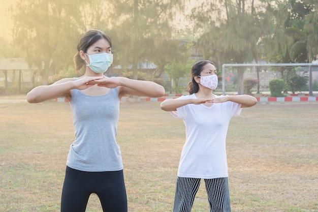Due donne che indossano maschere che esercitano la mattina nel parco e la natura solare. e buona salute per il nuovo stile normale e di vita