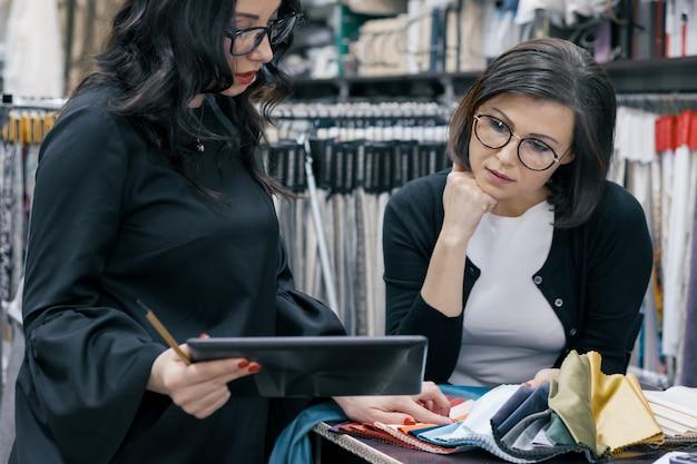 Due donne che lavorano con tessuti per interni