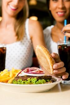 Due donne che mangiano hamburger e bevono soda