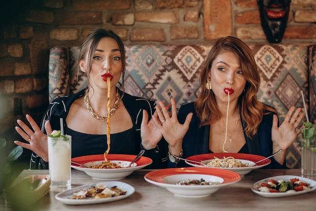 Due donne che mangiano pasta in un ristorante italiano