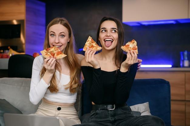 Due donne che si divertono a casa, aprendo la scatola della pizza, consegna del cibo, festa a casa