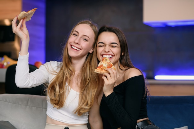 Due donne che si divertono a casa, aprendo la scatola della pizza, la consegna del cibo, la festa a casa