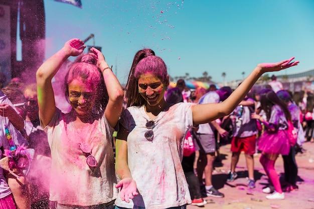 Due donne che si divertono e giocano con la polvere di holi