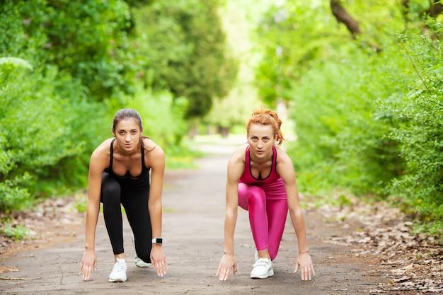 Due donne che si esercitano nel parco. giovane bella donna che fa le esercitazioni insieme all'aperto