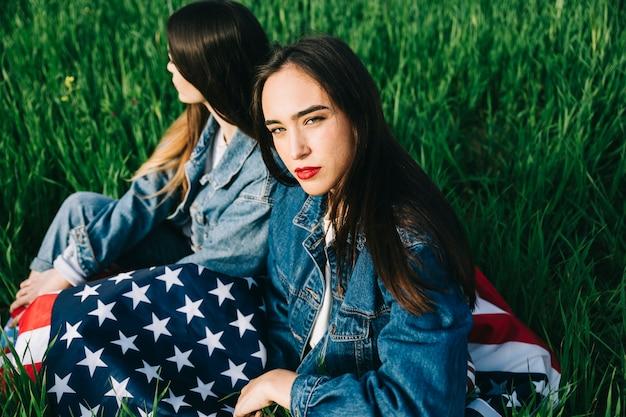 Due donne che si siedono sull'erba