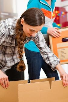 Due donne con la scatola commovente nella sua casa