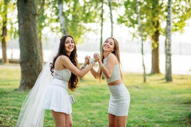 Due donne degli amici divertendosi sul parco al addio al nubilato.