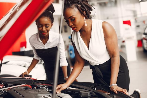 Due donne di colore alla moda in un salone di auto