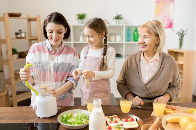 Due donne e bambine felici che preparano frullato fresco in miscelatore elettrico per la prima colazione