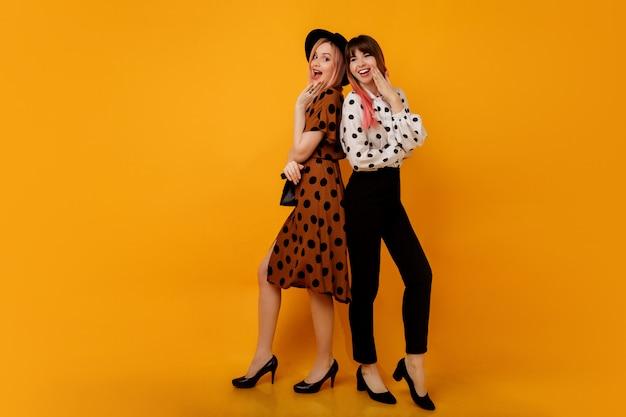 Due donne eleganti e alla moda in abiti in posa sul muro giallo