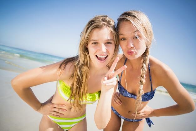 Due donne felici che fanno il broncio e che gesturing sulla spiaggia