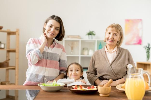 Due donne felici e bambina ti guardano mentre andando a preparare una cena sana festiva