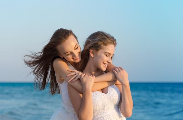 Due donne in abito bianco sulla spiaggia