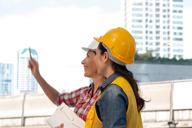 Due donne lavoratrici stanno lavorando insieme al cantiere