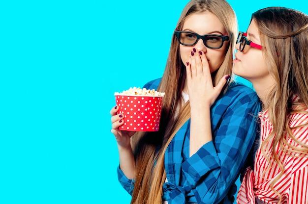 Due donne mangiano popcorn in bicchieri 3d
