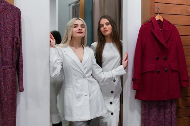 Due donne nella boutique della moda scelgono il vestito una stilista professionista aiuta i clienti a scegliere i vestiti. sconti di sconto di acquisto di festa di stagione vendita due amiche caucasiche camminano lo spogliatoio del centro commerciale