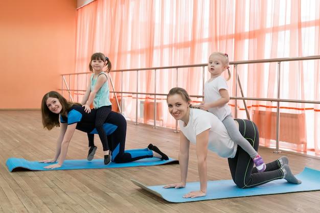 Due donne praticano sport con i loro bambini.