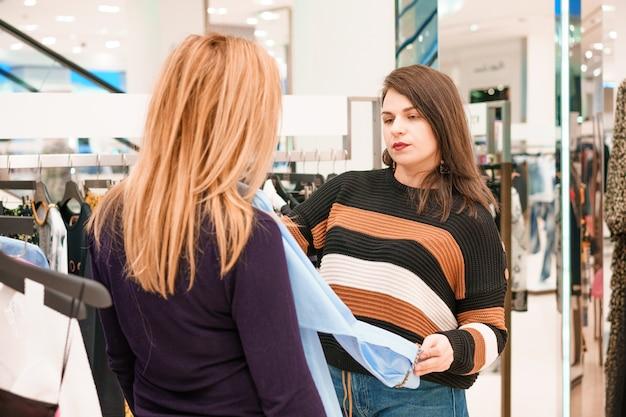 Due donne scelgono i vestiti in un negozio