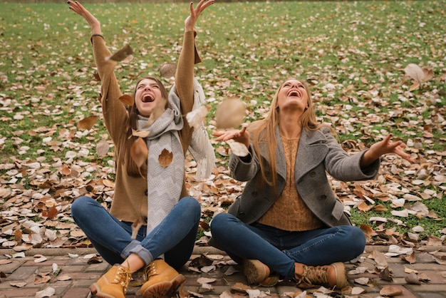 Due donne sedute e giocando con le foglie nel parco