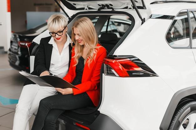 Due donne sedute nella parte posteriore della macchina e guardando nel documento.