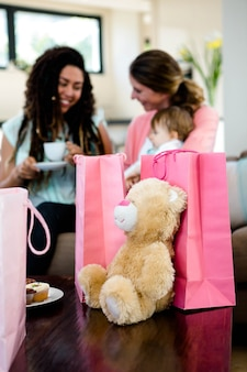 Due donne sedute su un divano con un bambino circondato da regali