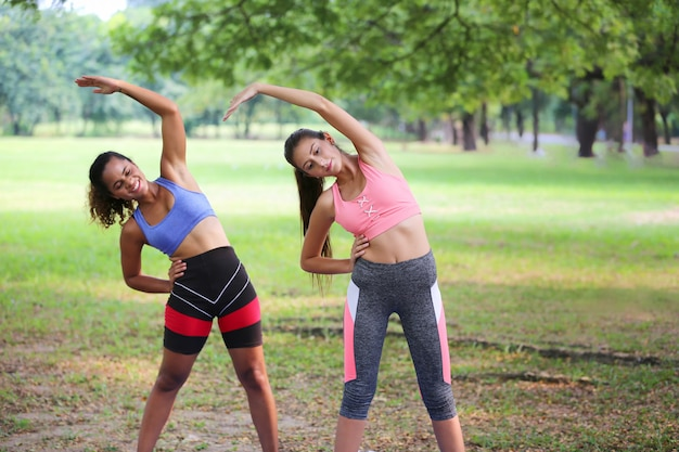 Due donne si divertono a scaldarsi insieme nel parco dopo l'esercizio e il jogging