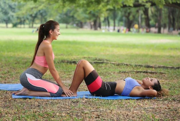 Due donne si godono il corpo seduti insieme nel parco dopo l'esercizio e il jogging