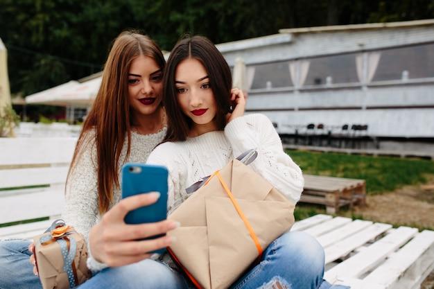 Due donne si siedono su una panchina all'esterno e sparano regali per smartphone