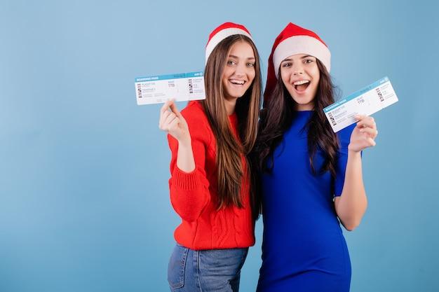 Due donne sorridenti che indossano i cappelli di santa con i biglietti aerei isolati sopra il blu