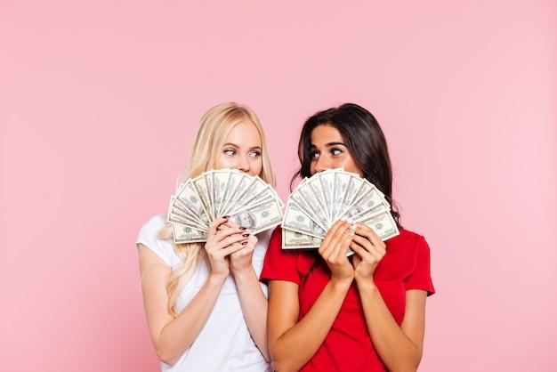 Due donne sorridenti che si nascondono dietro i soldi e che guardano l'un l'altro sopra il rosa