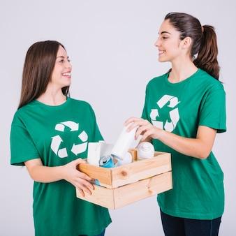 Due donne sorridenti che tengono la scatola di legno con riciclano gli oggetti