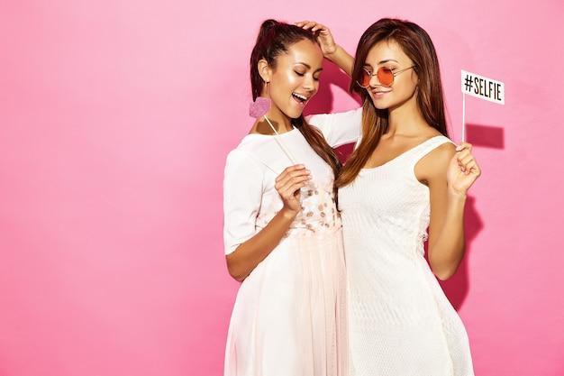 Due donne sorridenti divertenti sorprese con grandi labbra e selfie sul bastone. concetto intelligente e di bellezza. giovani modelle allegre pronte per la festa. donne isolate sulla parete rosa. femmina positiva