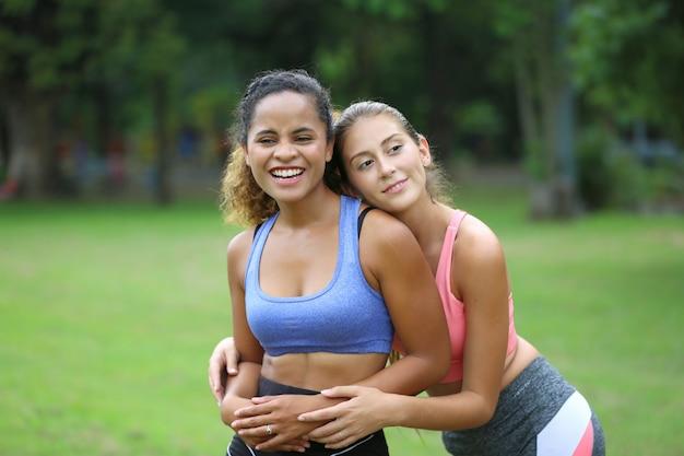 Due donne sorridenti in abbigliamento sportivo si divertono insieme nel parco