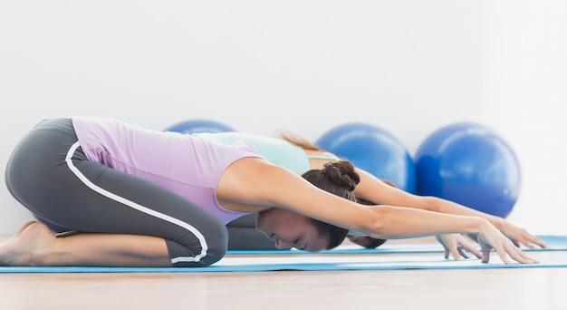 Due donne sportive nella meditazione pongono al centro fitness