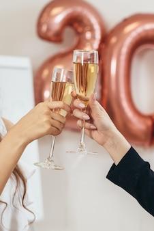 Due donne tintinnano bicchieri durante le vacanze. le mani si chiudono. celebrazione.