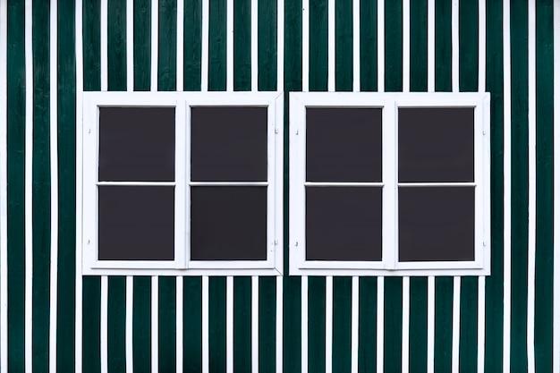 Due doppie finestre bianche su una parete verde con doghe bianche.
