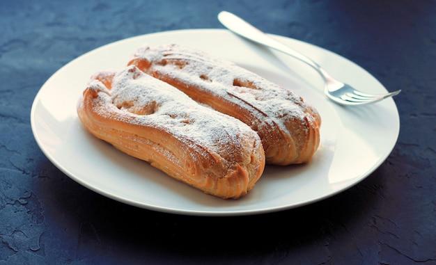 Due eclairs con zucchero a velo su un piatto bianco, con una forchetta, su uno sfondo scuro.