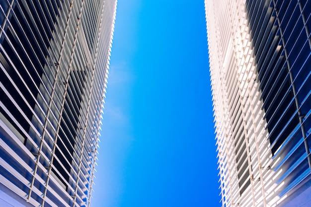 Due edifici convergenti su un cielo blu